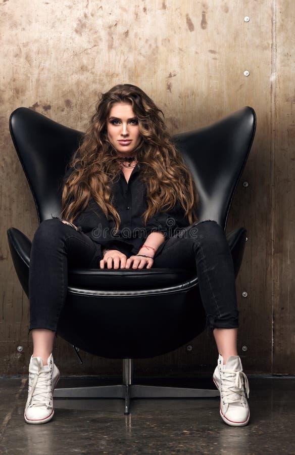 Vertikales Porträt einer herrschsüchtigen jungen Frau, die im schwarzen Stuhl sitzt lizenzfreie stockfotografie