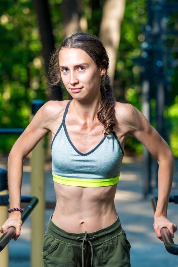 vertikales Porträt einer muskulösen Frau, die an der Turnhalle im Park während aufwirft lizenzfreie stockfotos