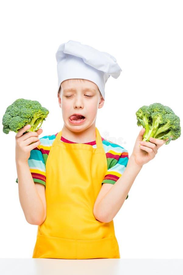 vertikales Portr?t eines Jungen, der nicht Brokkoli in der Kappe eines Kochs auf einem wei?en mag lizenzfreie stockfotos