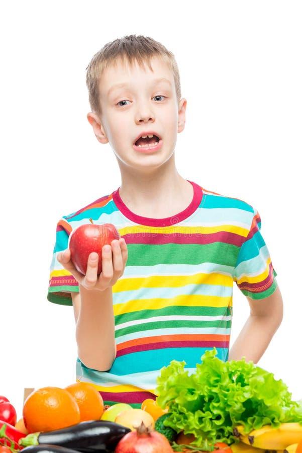 Vertikales Portr?t eines Jungen mit einem roten reifen Apfel im Studio auf wei?em Hintergrund lizenzfreie stockbilder
