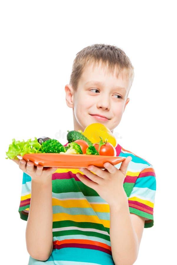 vertikales Porträt eines Jungen mit einer Platte des Gemüses auf Weiß stockbilder