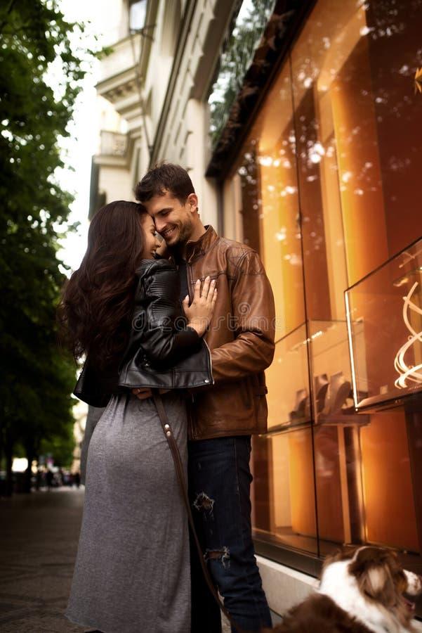 Vertikales Porträt von glücklichen reizenden Paaren stehen nah an einander, haben Weg mit Hund, genießen Zusammengehörigkeit und  stockbild