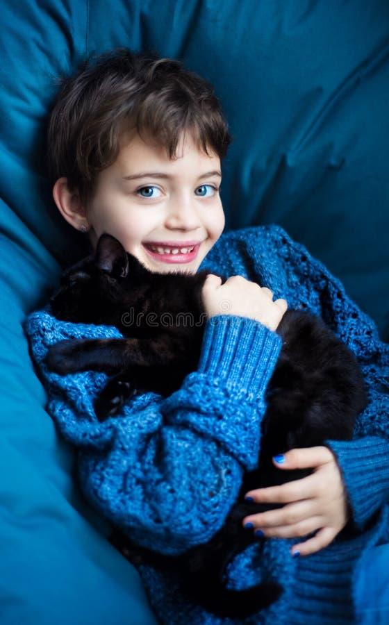 Vertikales Portrait von 7-jähriger lächelnder Mädchen mit kurzen Haarschnitt auf klassisch blauen Stuhl in klassisch blauen Pullo lizenzfreie stockfotografie