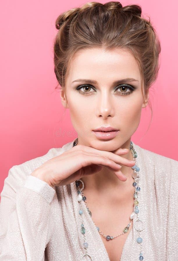 Vertikales Schönheitporträt der schönen jungen Frau in einer hellen Bluse mit Perlen auf dem Hals lizenzfreie stockbilder
