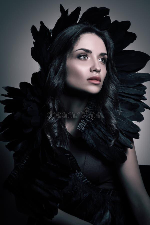 Vertikales Schönheitsporträt in den dunklen Tönen Junge Luxusfrau mit schwarzen Federn in ihrem Haar lizenzfreie stockfotos