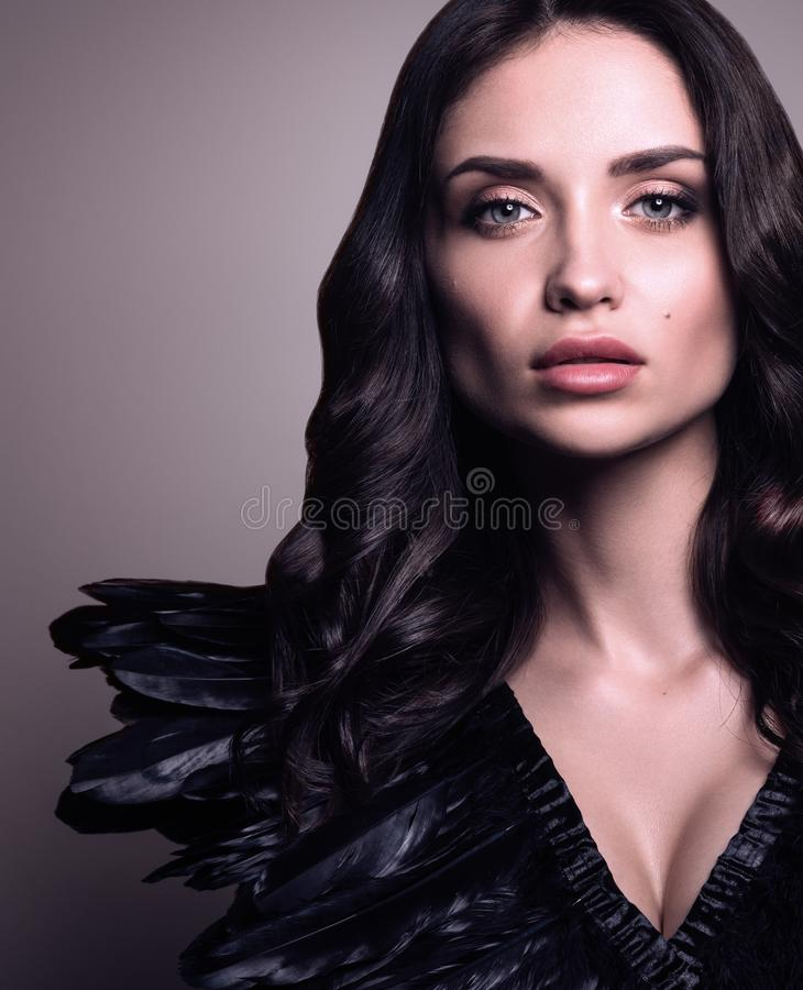 Vertikales Schönheitsporträt der jungen Schönheit in der Kleidung mit schwarzen Federn stockbild