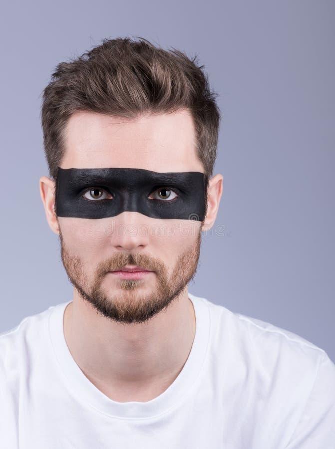 Vertikales Schönheitsporträt eines Mannes Ein junger Mann mit einem schwarzen stri stockfotografie