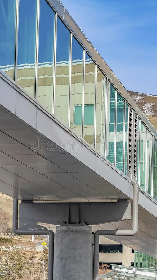 Vertikales Skybridge angeschlossen an ein modernes Gebäude mit Gebirgs- und des blauen Himmelshintergrund stockbilder