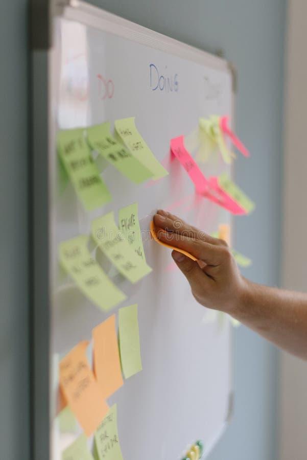 Vertikalt closeupskott av en person som klibbar färgrika klibbiga anmärkningar på en whiteboard arkivbild