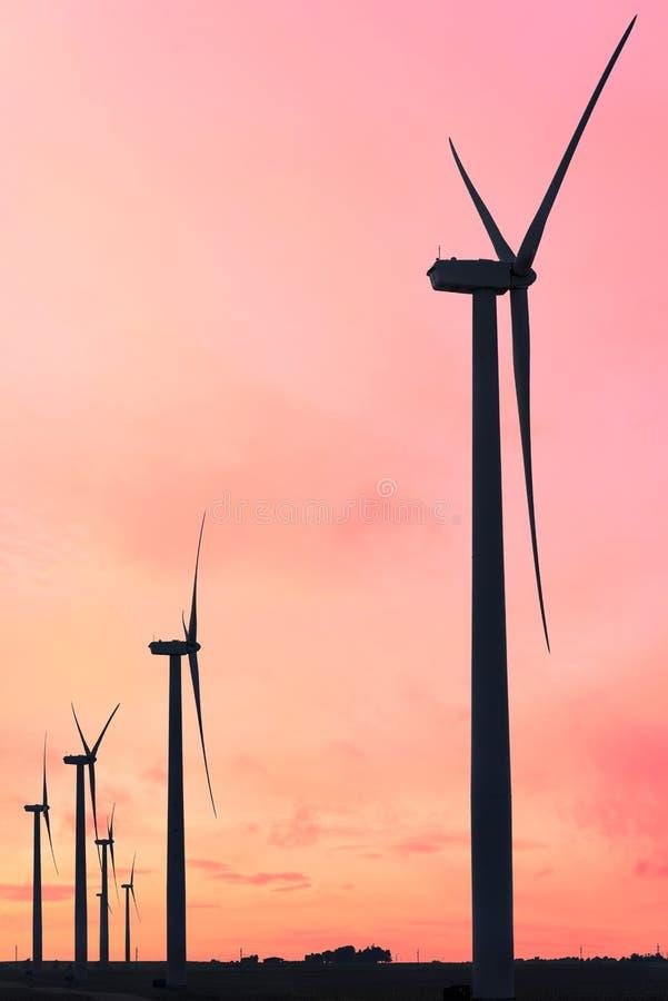 Vertikalt format av konturer av vindturbiner på en lantgård i Iowa på en solnedgånghimmel arkivbild