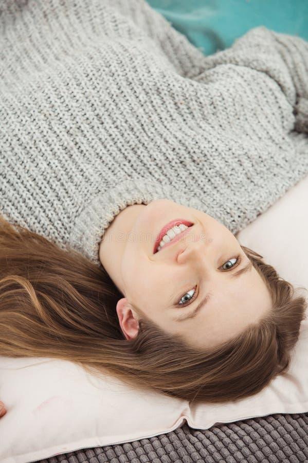 Vertikalt foto av att le den uppochnervända gulliga kvinnan arkivfoto