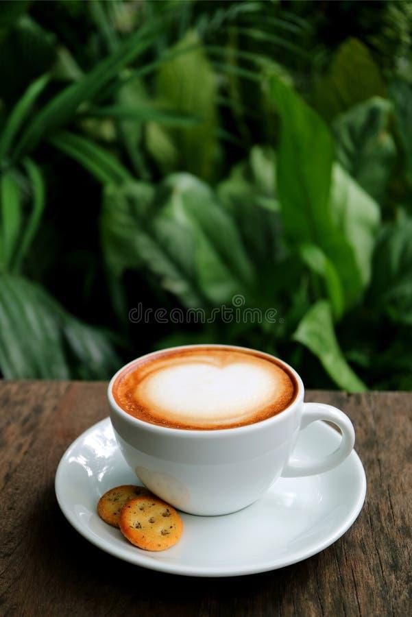 Vertikalt foto av en kopp av varmt cappuccinokaffe med kakor som tjänas som på trätabellen royaltyfri foto