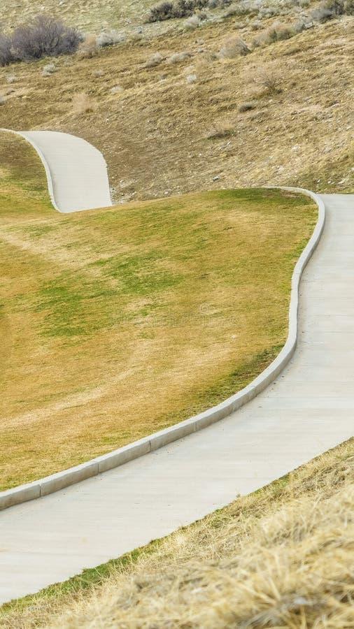 Vertikalt ramslut upp av en stenlagd bana som kör till och med lutningen av ett berg royaltyfri fotografi