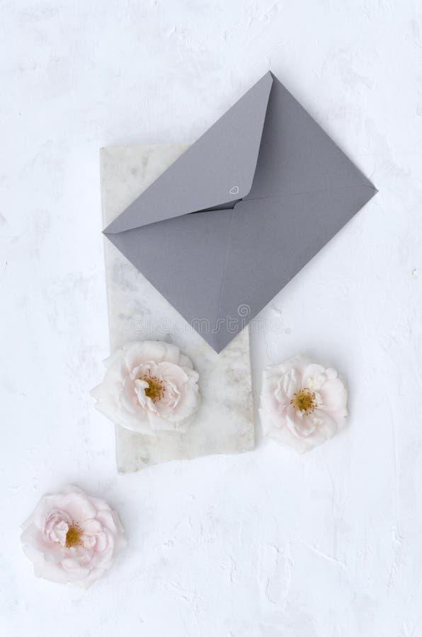 Vertikalt skott av det gråa kuvertet på marmorstenen, rosa mjuka rosor på den vita bakgrunden royaltyfria foton