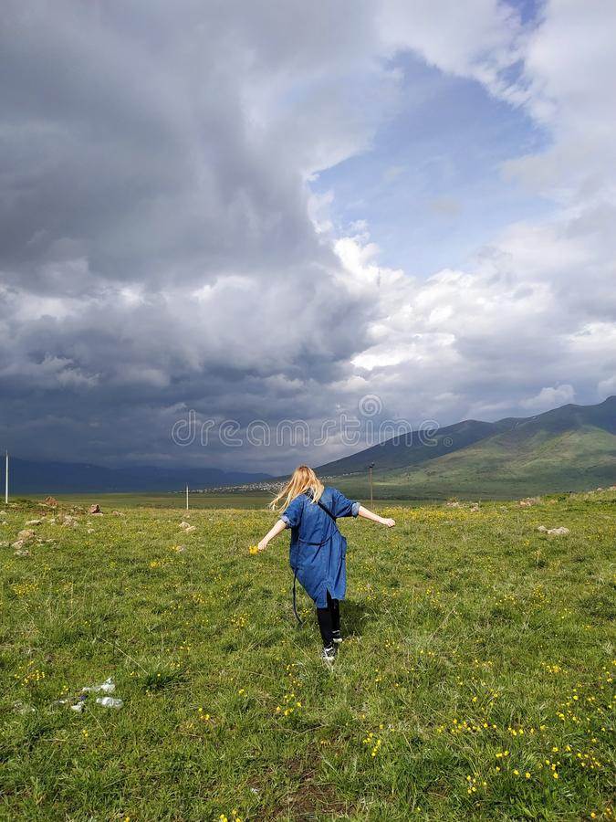 Vertikalt skott av en blond kvinnlig dans i ett stort härligt fält med att förbluffa moln i himlen arkivbilder