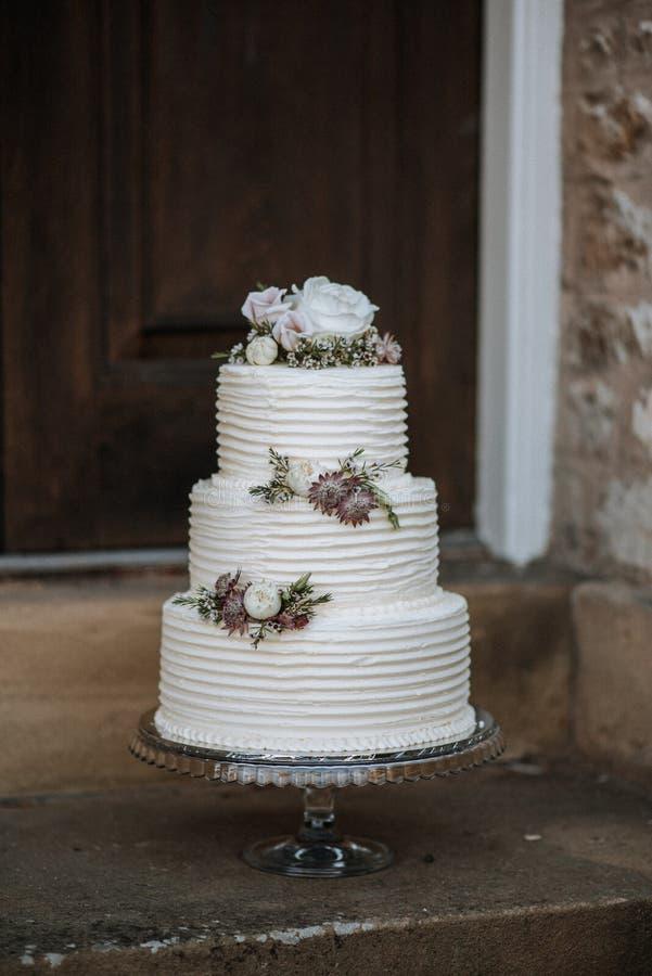 Vertikalt skott av en dekorerad tre-lager bröllopstårta med blommor på ett silveruppläggningsfat arkivbild