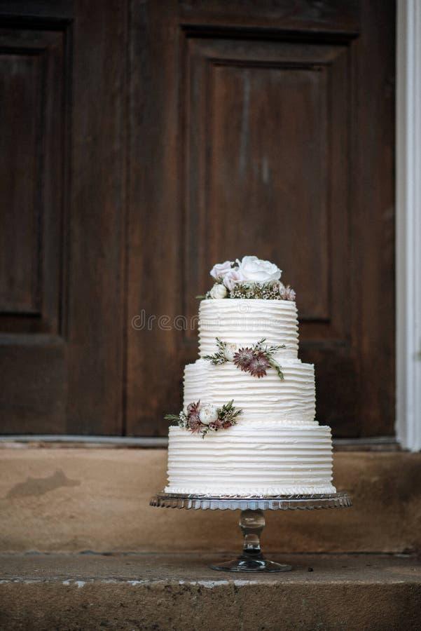 Vertikalt skott av en dekorerad tre-lager bröllopstårta med blommor på ett silveruppläggningsfat royaltyfri fotografi