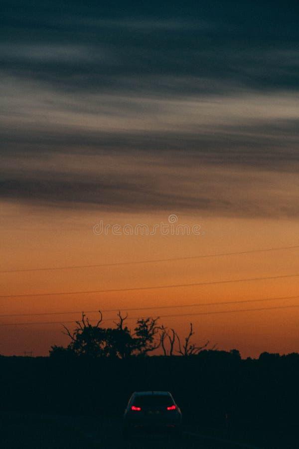 Vertikalt skott av en härlig solnedgång med en bil med ljus på royaltyfri fotografi