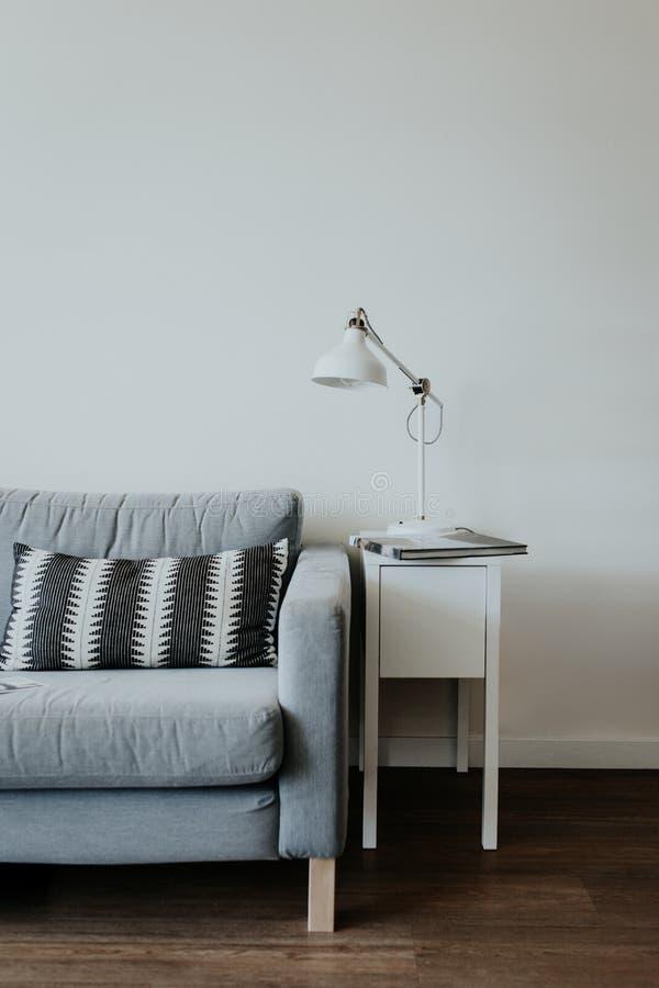 Vertikalt skott av en inre av det moderna huset med en soffa och en lampa på en nightstand royaltyfria bilder