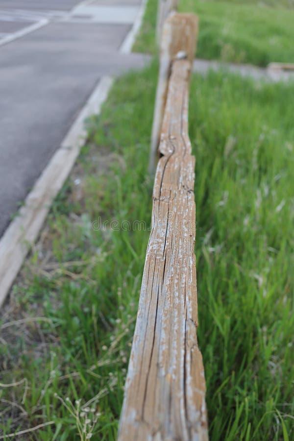 Vertikalt skott av ett trästaket på ett gräs- fält nära vägen royaltyfri bild