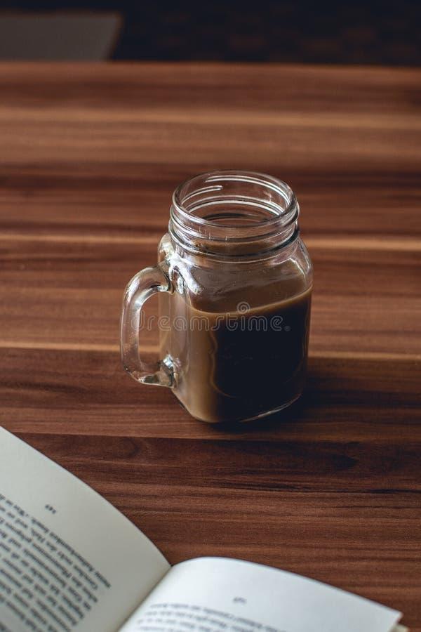 Vertikalt skott för Closeup av en exponeringsglaskopp av varm choklad på en trätabell royaltyfria bilder