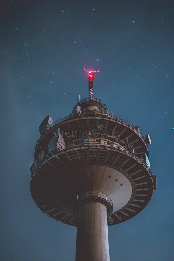 Vertikalt skott för låg vinkel av ett grått högväxt torn på natten med härliga stjärnor i bakgrunden royaltyfri fotografi