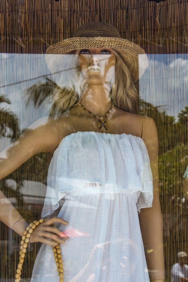 Vertoning en bezinning in Key West-winkelvenster van mooi wijfje manniquin met witte kleding en strohoed tegen bamboegordijn royalty-vrije stock foto's