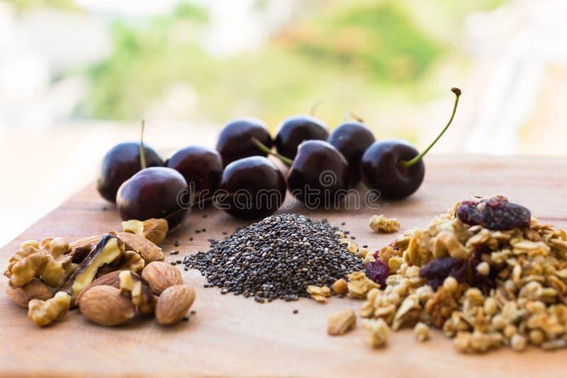 Vertoning van gezonde graangewas, noten, chiazaden, en kersen voor ontbijt royalty-vrije stock foto's