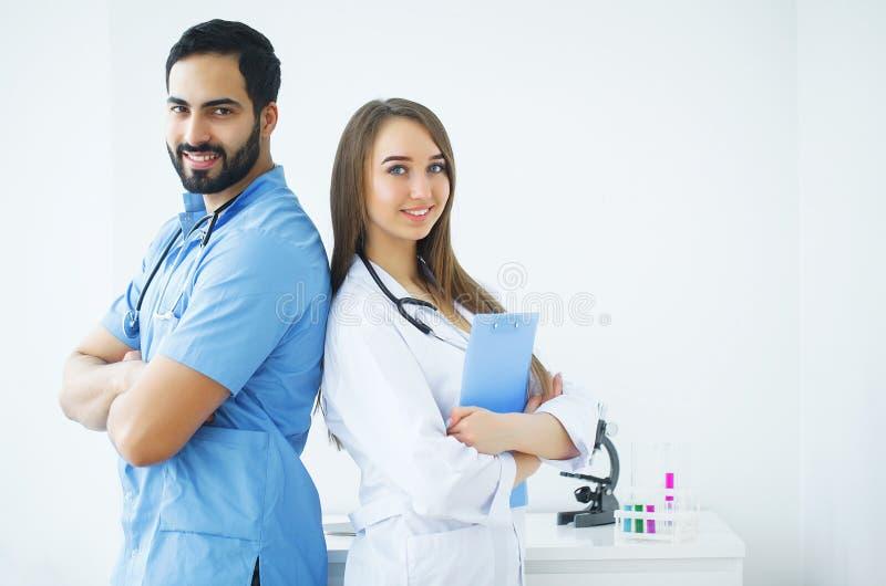 Vertragingen en wapens De aantrekkelijke artsen met medische stethoscoop werken aan stock afbeeldingen