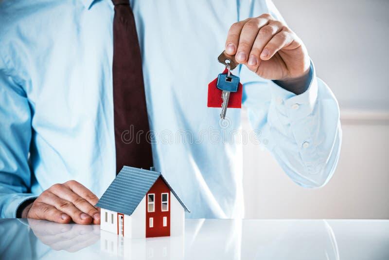 Vertreter Holding Key mit Miniaturhaus auf dem Tisch stockbilder