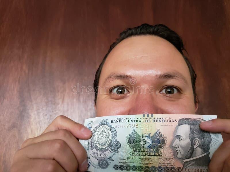 Vertretung des jungen Mannes und Halten der honduranischen Banknote von fünf Lempira stockfotografie