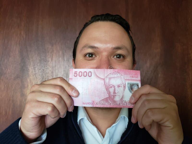 Vertretung des jungen Mannes und Halten einer chilenischen Banknote lizenzfreies stockfoto
