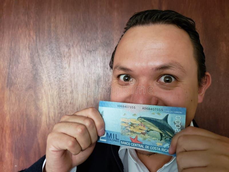 Vertretung des jungen Mannes und Halten einer Costa Rican-Banknote von colones 2000 stockfotos