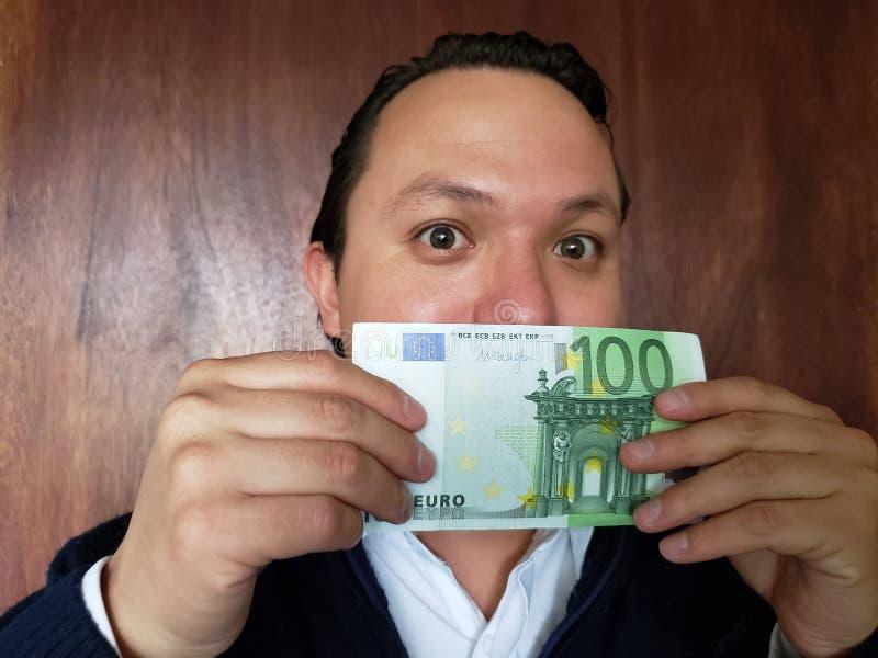 Vertretung des jungen Mannes und Halten einer europäischen Banknote stockfotos