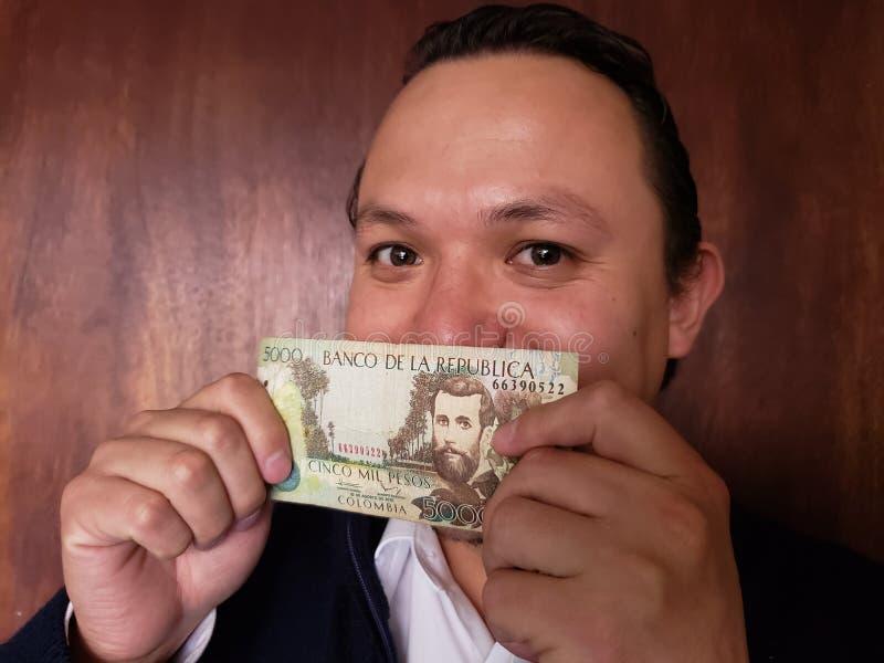 Vertretung des jungen Mannes und Halten einer kolumbianischen Banknote von 5000 Pesos lizenzfreies stockbild
