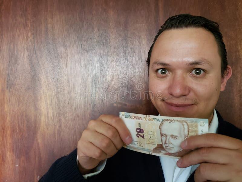 Vertretung des jungen Mannes und Halten einer peruanischen Banknote von zwanzig Sohlen lizenzfreie stockbilder