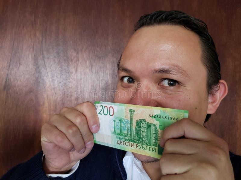 Vertretung des jungen Mannes und Halten einer russischen Banknote von 200 Rubeln lizenzfreie stockfotografie