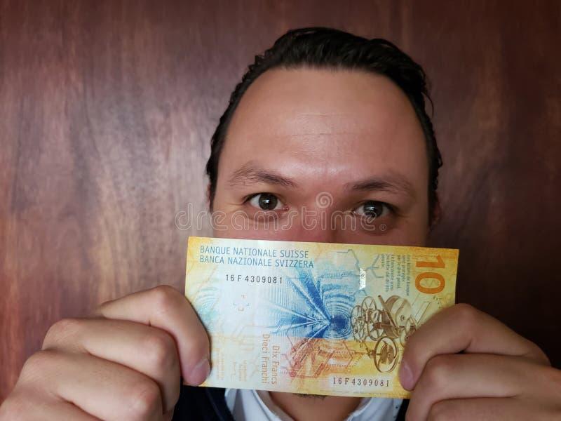 Vertretung des jungen Mannes und Halten einer Schweizer Banknote von zehn Franken stockfotografie