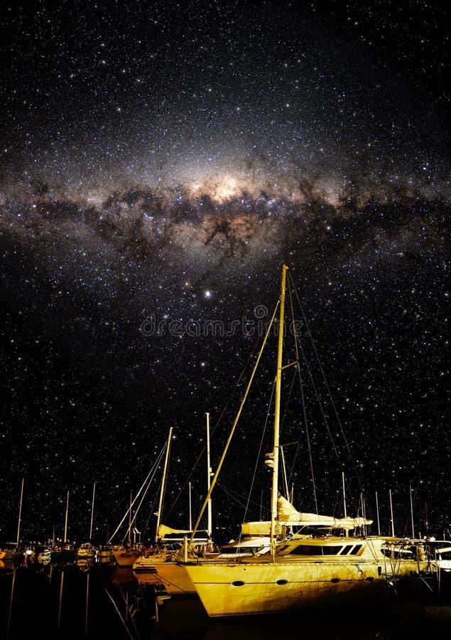 Vertretungssterne des nächtlichen Himmels und Milchstraße mit Booten im Vordergrund lizenzfreies stockbild