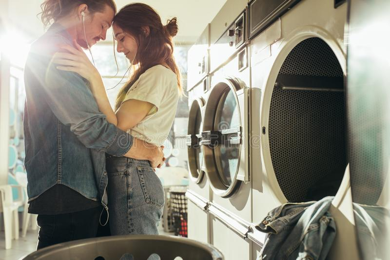 Vertrouwelijk paar die zich in wasserijruimte bevinden royalty-vrije stock fotografie