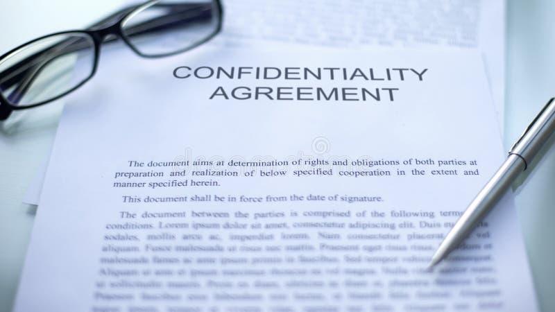Vertrouwelijkheidsovereenkomst, die over lijst, pen en oogglazen op document liggen stock fotografie