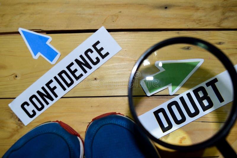 Vertrouwen of Twijfel tegenover richtingstekens in het overdrijven met tennisschoenen en oogglazen op houten royalty-vrije stock foto