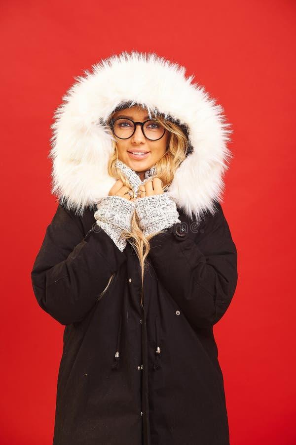 Verttical odizolowywał strzał piękna blond kobieta w czarnej zimy kurtce z kapiszonem, uśmiechy, szczerych uczucia zdjęcie stock