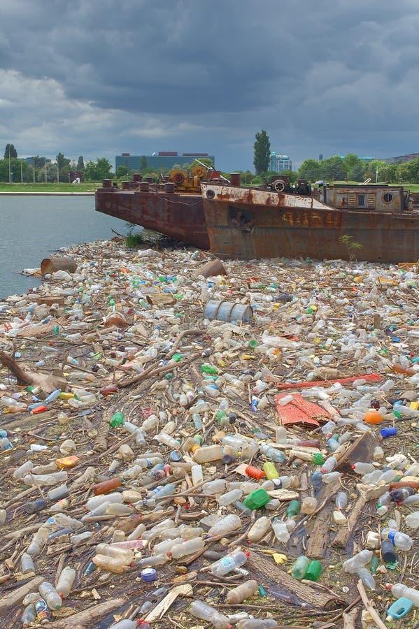 Verunreinigte Flussbank voll des Abfalls lizenzfreie stockfotos