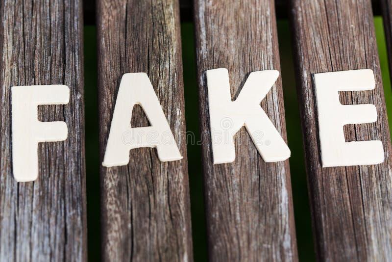Vervalsing, feit, als tekst, brieven op hout stock fotografie