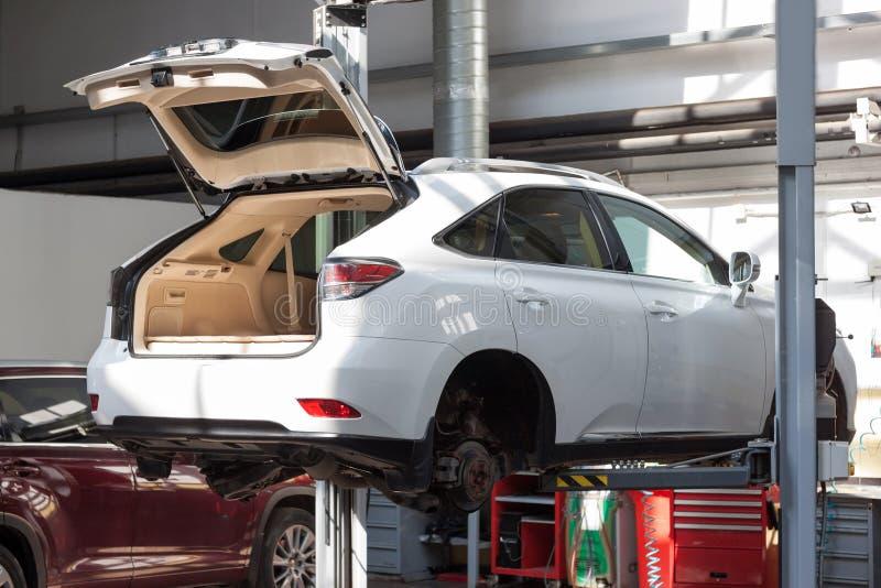 Vervangingswielen in workshopauto Het gebruiken van een hydraulische lift royalty-vrije stock afbeelding