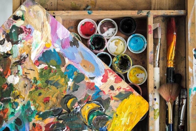 Verven van verschillende kleuren en vuile borstels op de schildersezel van het kunstenaarsclose-up stock foto's