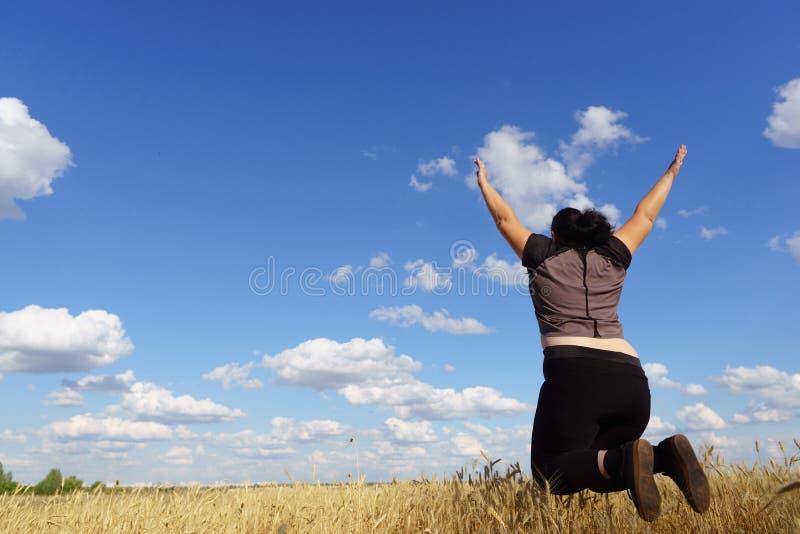 ?verviktig kvinna som hoppar p? himmelbakgrund arkivbild