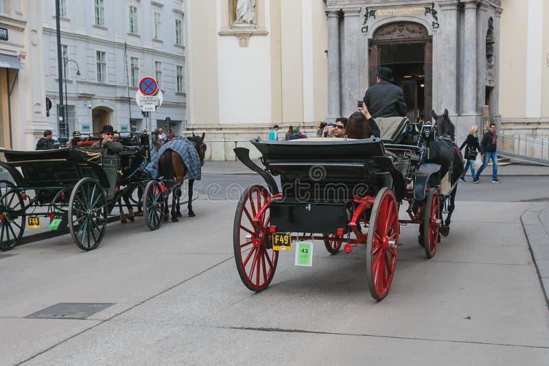 Vervoer met paarden, bestuurder en toeristen in Wenen op een sightseeingsreis rond de stad stock afbeeldingen
