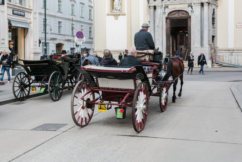 Vervoer met paarden, bestuurder en toeristen in Wenen op een sightseeingsreis rond de stad stock foto